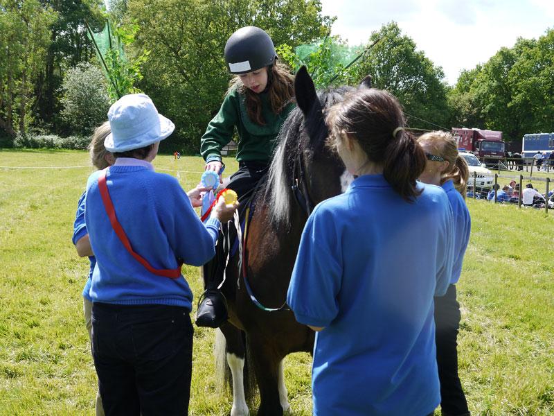 Girl on coloured pony receiving blue rosette