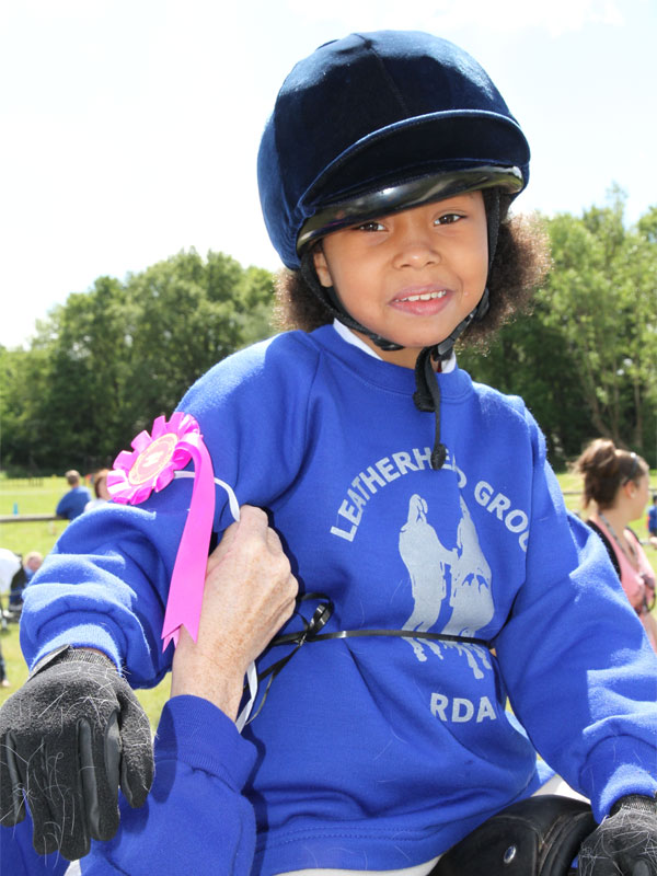 Girl on pony receiving pink rosette