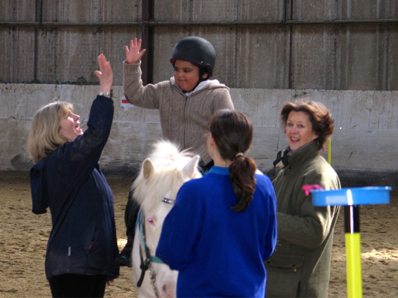 Boy on grey pony giving a volunteer a 'high five'