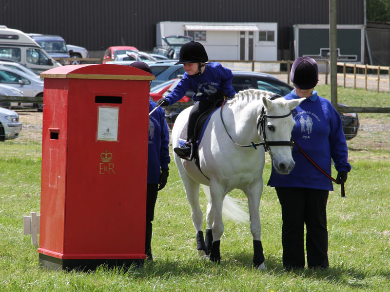 Girl on grey pony posting a letter