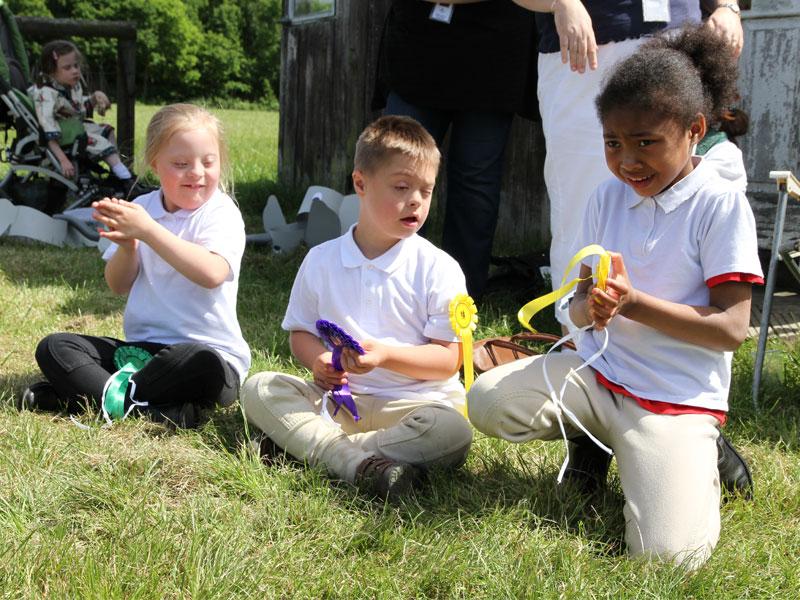 Three children holding rosettes