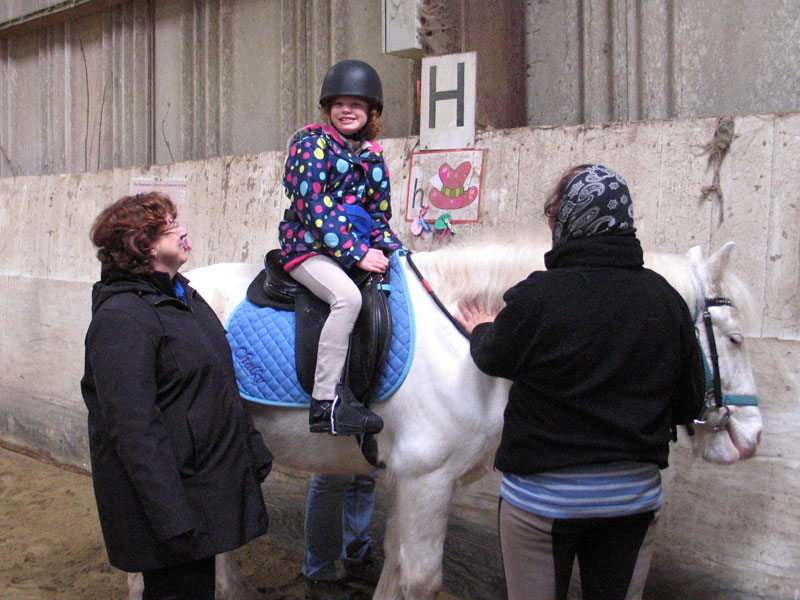 Girl on grey pony smiling for the camera