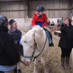 Girl on grey pony finding an Easter Egg