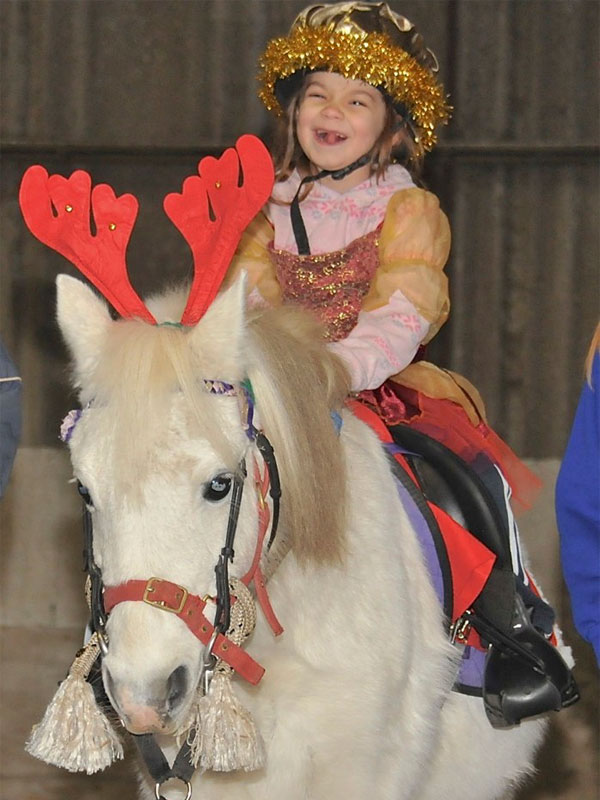 Girl on grey pony dressed as a sugar plum fairy pulling a funny face!