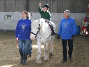 Child riding grey horse with leader and 2 sidewalkers
