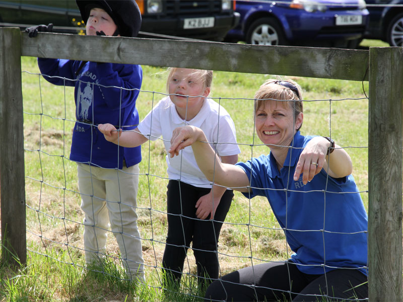 An adult and two children watching the competition through a fence