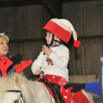 Child in Christmas pyjamas on pony yawning!
