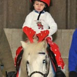 Child in Christmas pyjamas on pony