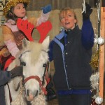 Girl on grey pony putting a star on the Christmas tree