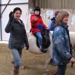 Girl on grey pony waving at camera
