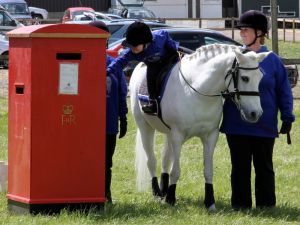 Girl on grey pony posting letter at RDA South East Region Fun Day