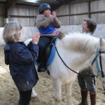 Boy clapping on grey pony